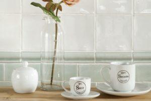 Vægfliser med bort og hvide kaffekopper